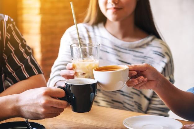 Close-up beeld van drie mensen rammelende koffiekopjes op houten tafel in café