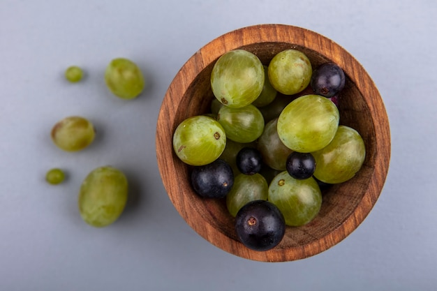 Close-up beeld van druiven bessen in kom en op grijze achtergrond