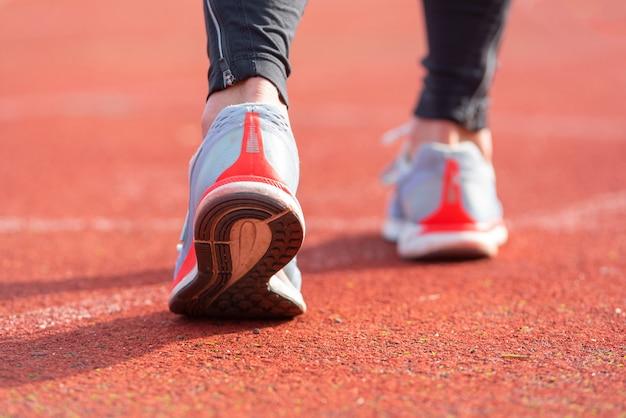 Close-up beeld van een atleet zich klaar voor de race op een renbaan. focus op schoen van een atleet die binnenkort een race in het stadion begint.