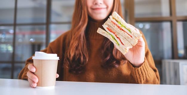 Close-up beeld van een aziatische vrouw met volkoren broodje en koffiekopje