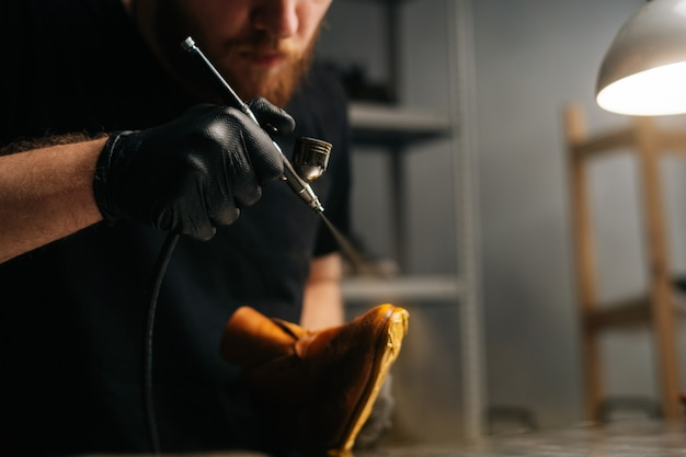 Close-up beeld van een bebaarde schoenmaker met zwarte handschoenen die verf spuit van lichtbruine leren schoenen c...