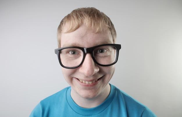 Close-up beeld van een blanke man die een blauw t-shirt en een bril draagt en grappige gezichtsgebaren maakt