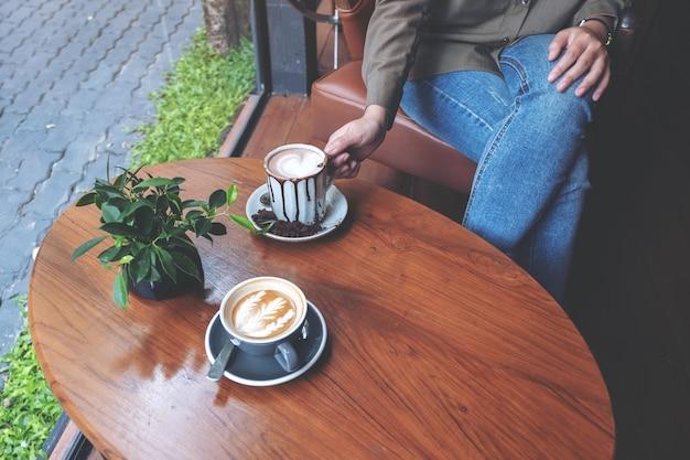 Close-up beeld van een hand met een kop warme chocolademelk met een ander kopje koffie op houten tafel in café