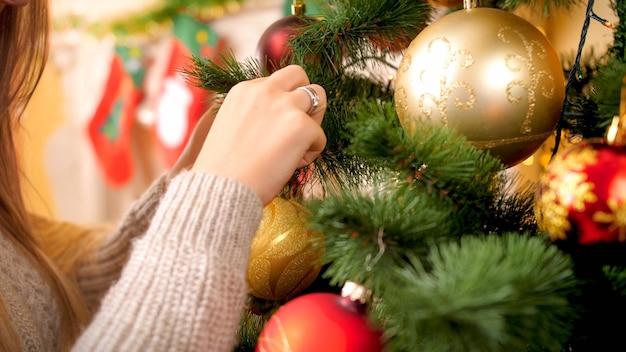 Close-up beeld van een jonge vrouw in wollen trui die de kerstboom versiert met kerstballen en slingers