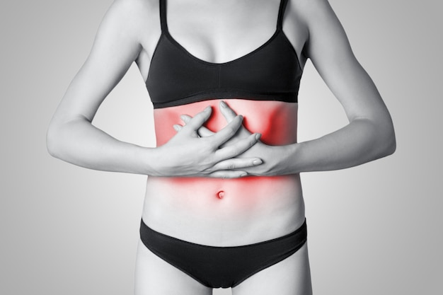 Close-up beeld van een jonge vrouw met maagpijn of spijsvertering of menstruatiecyclus op grijze achtergrond. zwart-wit foto met rode stip.