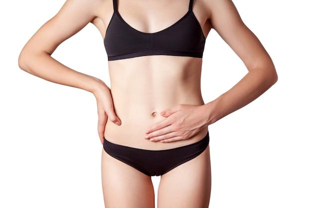 Close-up beeld van een jonge vrouw met maagpijn of spijsvertering of menstruatiecyclus op witte achtergrond.
