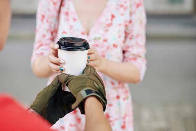 Close-up beeld van een koerier die een kopje afhaalkoffie geeft aan een jonge vrouw die het bij de plaatselijke coffeeshop bestelde