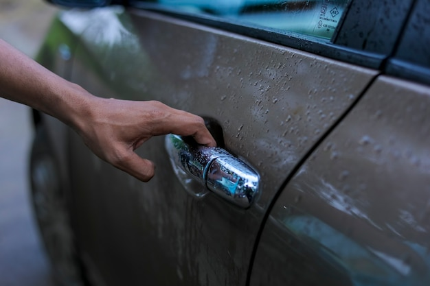 Close-up beeld van een man opent de deur van de auto.