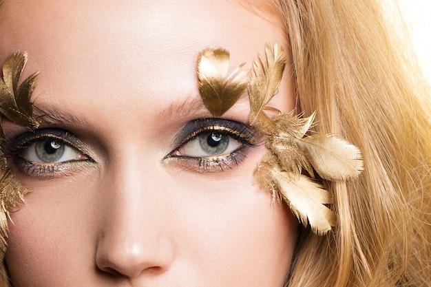 Close-up beeld van een meisje met een mooie make-up en gouden veren. luxe uitstraling.