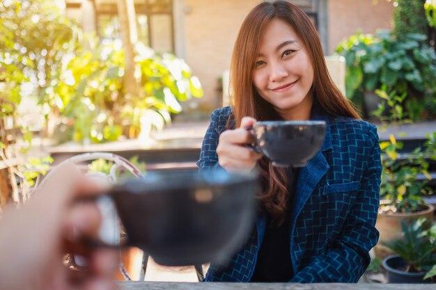 Close-up beeld van een mooie aziatische vrouw rammelende koffiemokken met vriend in café