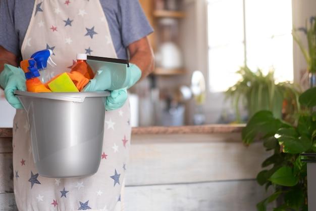 Close-up beeld van een plastic emmer met schoonmaakartikelen voor thuis senior man houdt de emmer vast