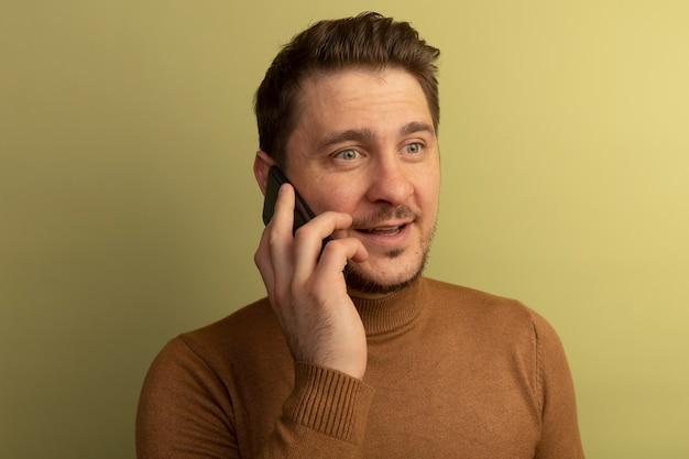 Close-up beeld van een tevreden jonge blonde knappe man die er recht uitziet terwijl hij aan de telefoon praat