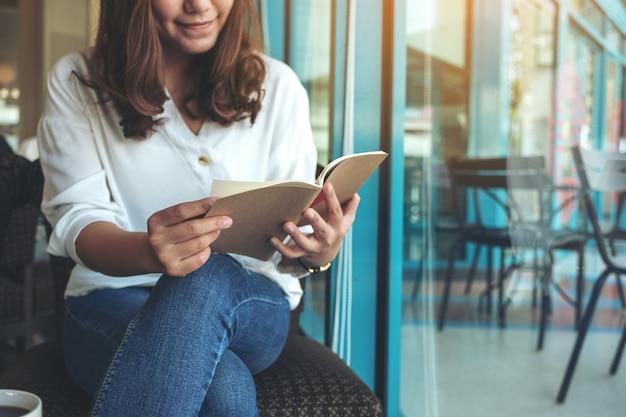 Close-up beeld van een vrouw die een boek opent om te lezen met notitieboekjes en koffiekopje op houten tafel in café