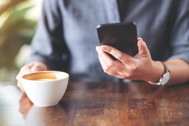 Close-up beeld van een vrouw die een mobiele telefoon vasthoudt en gebruikt terwijl ze koffie drinkt op houten tafel in café