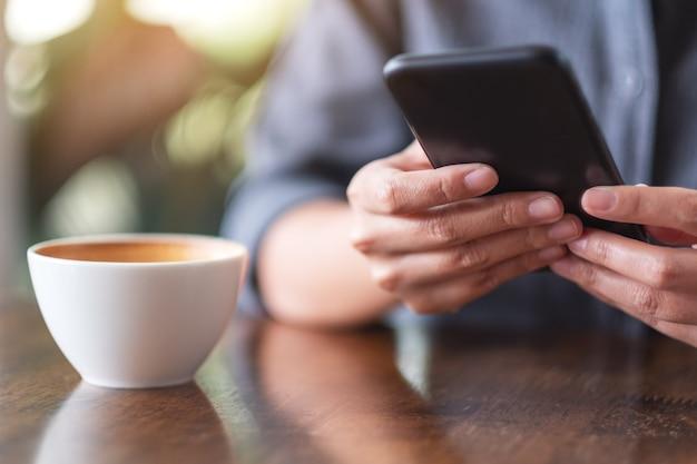 Close-up beeld van een vrouw die mobiele telefoon vasthoudt en gebruikt met koffiekopje op houten tafel in café