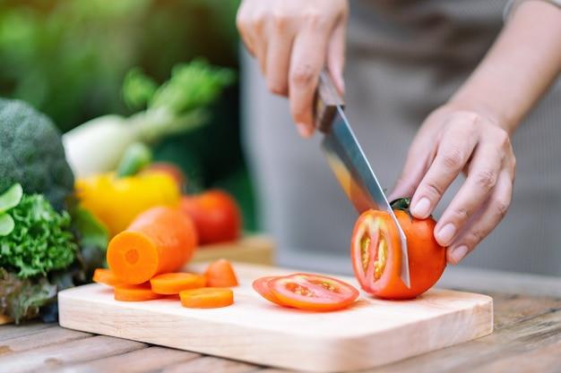 Close-up beeld van een vrouw die tomaat snijdt en hakt met een mes op een houten bord