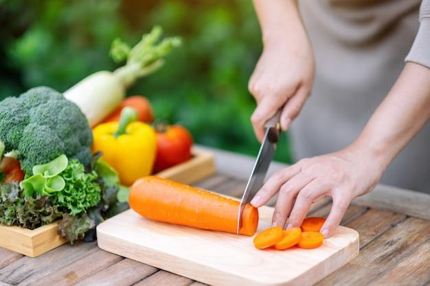 Close-up beeld van een vrouw die wortel snijdt en hakt met een mes op een houten bord