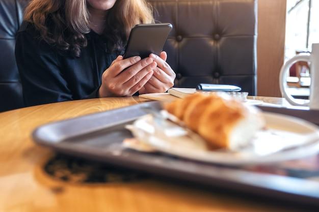 Close-up beeld van een vrouw houden, gebruiken en kijken naar slimme telefoon met brood op tafel zittend in café