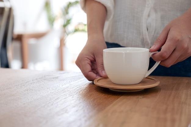 Close-up beeld van een vrouw met een witte kop warme koffie op houten tafel in café