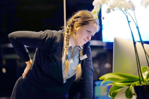 Close-up beeld van een vrouw-receptie werknemer hotelmanager met pijn in de nieren. rugpijn.