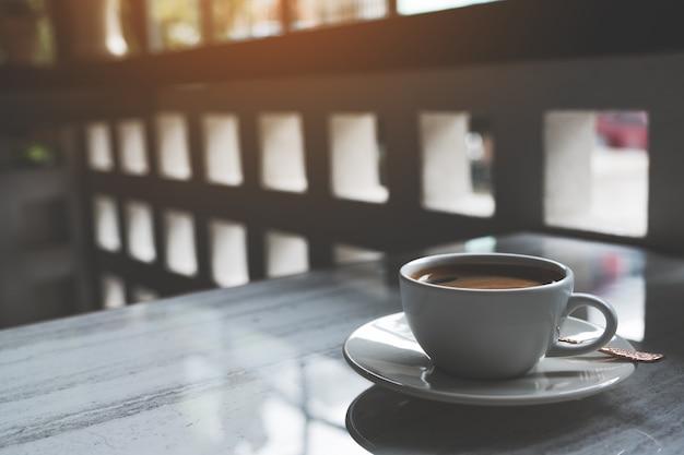 Close-up beeld van een witte kop warme koffie op tafel in café