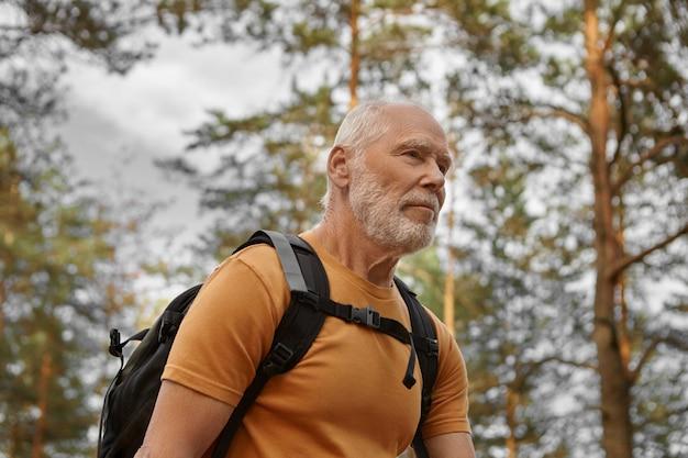 Close-up beeld van gelukkig bebaarde blanke mannelijke reiziger backpacken alleen, energiek kijken. stijlvolle actieve man backpacker wandelen met rugzak, genietend van een gezonde levensstijl en cardio-activiteit