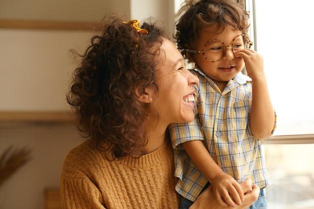Close-up beeld van gelukkige jonge golvende haired spaanse vrouw poseren door raam omarmen zoontje. leuke driejarige jongen die ronde oogglazen draagt, dag thuis doorbrengt. familie en relaties