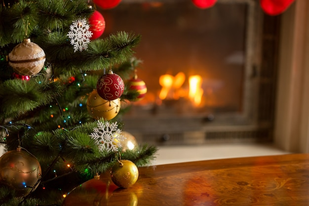 Close-up beeld van gouden en rode kerstballen op kerstboom voor brandende open haard. mooie kerstachtergrond