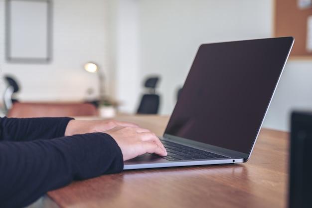 Close-up beeld van handen met behulp van en typen op laptop toetsenbord op houten tafel in kantoor