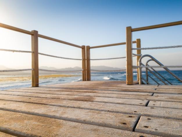 Close-up beeld van houten plank op de lange pier in de oceaan. perfect voor het invoegen van uw afbeelding of het plaatsen van een product. plaats voor tekst. ruimte kopiëren