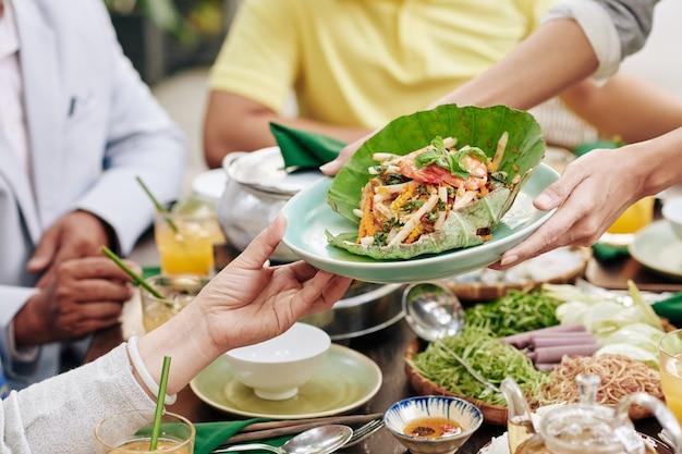 Close-up beeld van huisvrouw die bord met heerlijke zeevruchtensalade geeft aan gasten tijdens het diner