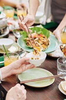 Close-up beeld van huisvrouw die deel van heerlijke zeevruchtensalade in kom van gast zet tijdens diner