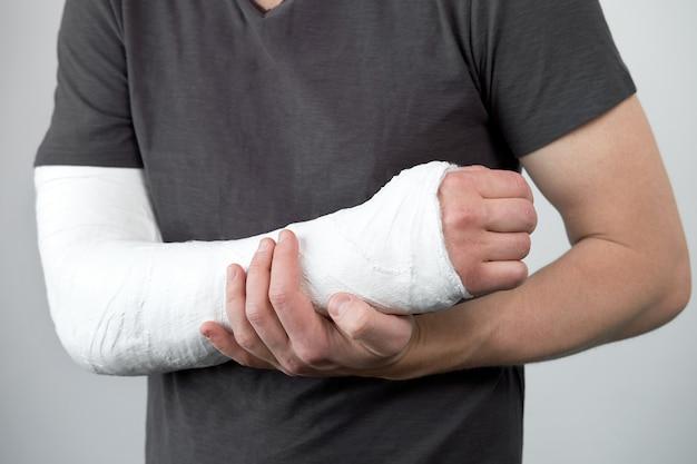 Close-up beeld van iemands hand met gipsverband op een witte muur