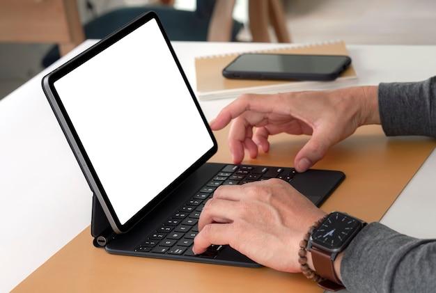 Close-up beeld van iemands handen werken op tablet met toetsenbord zittend aan tafel in de woonkamer.