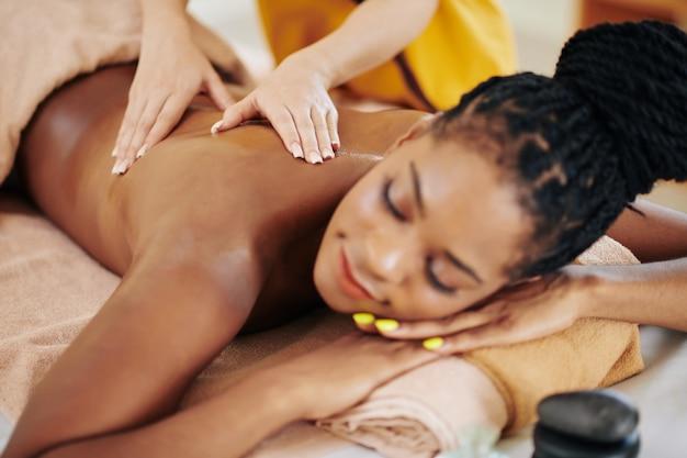 Close-up beeld van jonge afro-amerikaanse jonge vrouw krijgen spa lichaamsmassage behandeling in de schoonheidssalon