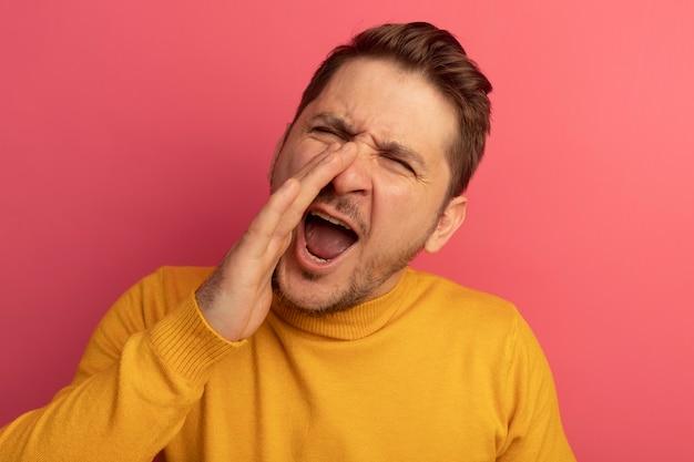 Close-up beeld van jonge blonde knappe man die hand in de buurt van mond houdt en hardop roept naar iemand geïsoleerd op roze muur