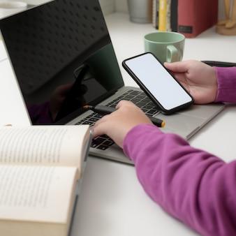 Close-up beeld van jonge collage meisje bezig met haar project tijdens het gebruik van haar smartphone