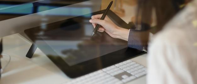Close-up beeld van jonge ontwerper bezig met haar concept met grafisch tablet, weergave door glas