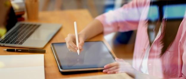 Close-up beeld van jonge student bezig met haar project met tablet, weergave door glas