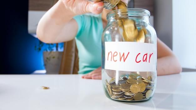Close-up beeld van jonge vrouw die geld verzamelt voor het kopen van een nieuwe auto. concept van financiële investeringen, economische groei en banksparen.