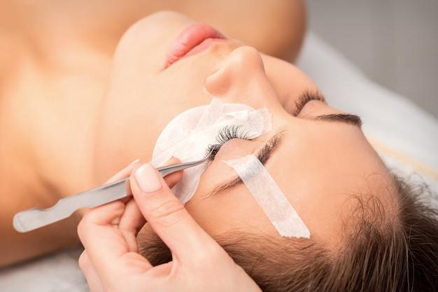 Close-up beeld van jonge vrouw met wimper extensie procedure in de schoonheidssalon