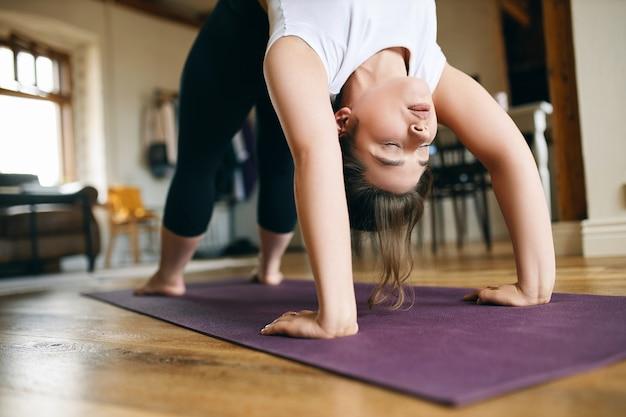 Close-up beeld van jonge vrouwelijke yogi die thuis geavanceerde yoga beoefent, opwaartse boog of wielhouding doet, achterover buigt, handen en voeten op de mat houdt, ruggengraat uitrekt en borst opent.