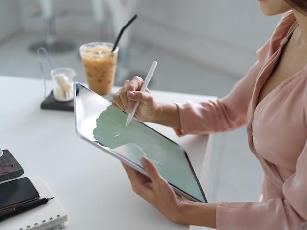 Close-up beeld van jonge zakenvrouw haar werk schaven op mock up tablet in kantoorruimte
