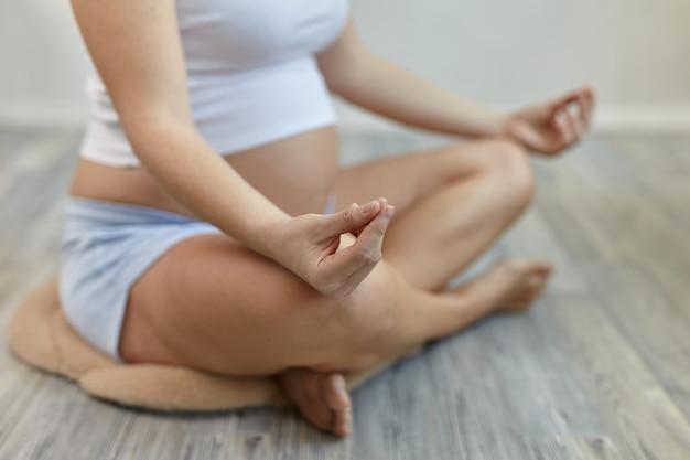 Close-up beeld van jonge zwangere vrouw die ochtend yoga-oefening doet na thuis wakker worden. yogi vrouwelijk model zit in kleermakerszit op de grond en mediteert