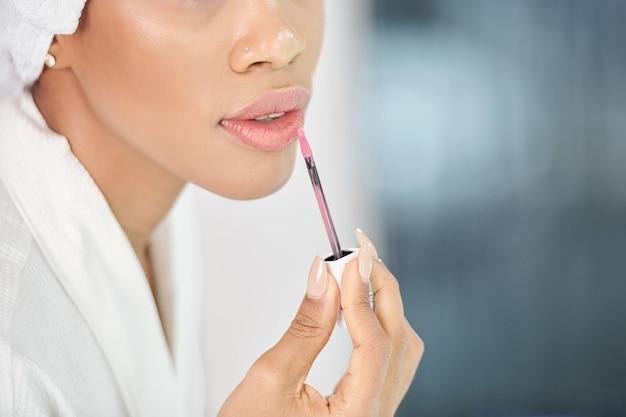 Close-up beeld van jonge zwarte vrouw die lichtroze plumping hydraterende lipgloss toepast