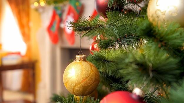 Close-up beeld van kerstboomtak versierd met slingers en gouden kerstballen tegen vuurpalce met sokken voor kerstcadeaus