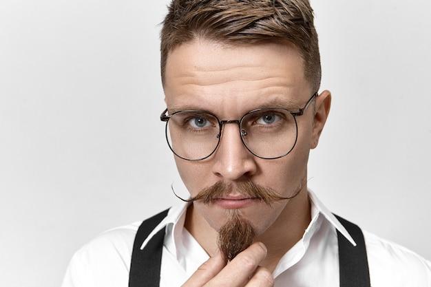Close-up beeld van knappe charmante europese man met blauw oog en stijlvolle snor zijn sikje baard aaien