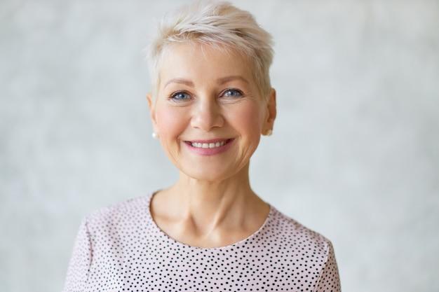 Close-up beeld van knappe mooie rijpe blonde vrouw met blauwe ogen, elegante make-up en pixiekapsel glimlachen, zelfverzekerd gelukkige gezichtsuitdrukking hebben, in goed humeur zijn