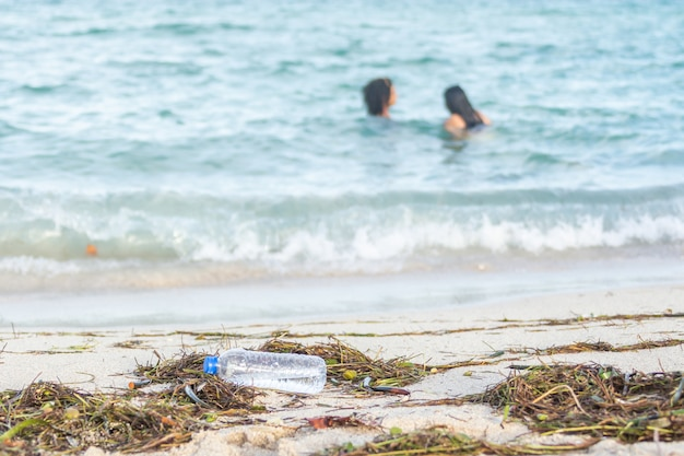 Close-up beeld van lege plastic fles water op vuile strand gevuld met zeewier, afval en afval op vuile zandstrand met mensen in zee