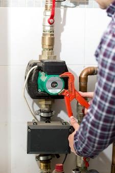 Close-up beeld van loodgieter die verwarmingssysteem repareert met rode tang